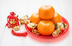 Chinese New year,ang pow red felt fabric bag with gold ingots an. D tangerine oranges with red tray on white wood table top,Chinese Language mean Happiness and stock images