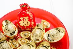 Chinese New year ang pow red felt fabric bag with gold ingots in. Red tray on white wood table top,Chinese Language on bag mean Happiness and on ingot mean stock photos