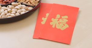 Chinese new year assorted snack tray with red pocket, red poacke. R with a chinese word meaning luck Stock Photo