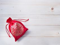 Red silky money bag with string on wood background Stock Photo