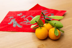 Chinese new year calligraphy and kumquat, word meaning is good l. Chinese new year calligraphy and kumquat on the wooden background , word meaning is good luck
