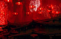 Chinese new year celebration chinese rooftops with lanterns in the sky and fireworks with red smoke amazing background royalty free stock photography