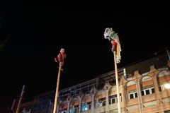 Chinese New Year celebration by traditional performance of lion on the top of bamboo pole at public street of downtown stock image