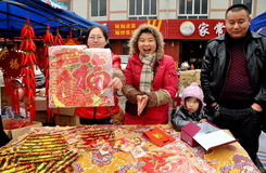 Chinese New Year Celebrations. Family selling colourful paper decorations for the annual Chinese New Year Spring Festival from a table in Long Xing Square in