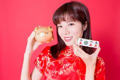 Chinese new year concept. Beauty woman hold Mahjong with golden pig bank - rich and 2019 ten thousand in chinese word royalty free stock images