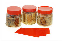 Chinese New Year cookies and red packets. Chinese New Year red packets and cookies in plastic containers Stock Image
