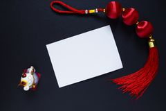 Chinese New Year dcer and blank paper card on black. Oriental lucky knot and maneki neko cat figurine. White paper card. Chinese Lunar New Year top view. Asian stock images
