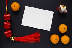 Chinese New Year decor and oranges on black background with blank postcard. Lunar New Year top view photo. Chinese red lucky knot. Asian winter holiday Stock Images