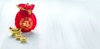 Chinese new year decoration,red fabric packet or ang pow with chinese style pattern and golden ingots on wood table top, Chinese royalty free stock photography