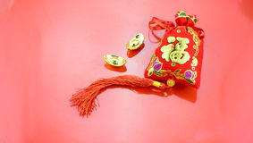 Chinese new year decoration: red felt fabric packet or ang pow w. Ith word prosperous and golden ingots on red fabric