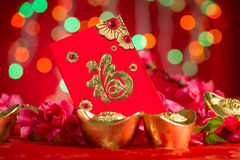Chinese New Year decorations gold ingots and red packet. Chinese new year festival decorations, red packet and gold ingots on red glitter background. Chinese