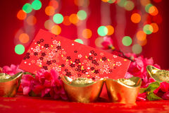 Chinese New Year decorations red packet and gold ingots. Chinese new year festival decorations, red packet and gold ingots on red glitter background royalty free stock photo