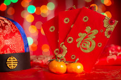 Chinese New Year decorations and red packets. Chinese new year festival decorations, red packet and mandarin orange on red glitter background. Chinese character royalty free stock photos