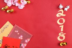 Miniature dogs with chinese new year decorations - series 8. Chinese new year decorations for year 2018 on red surface stock photo