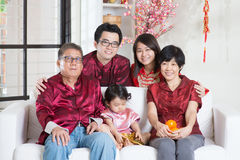 Chinese New Year with family. Chinese new year celebration. Happy Asian multi generations family in red cheongsam reunion at home