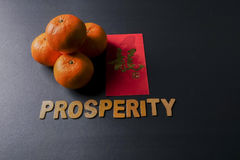 Chinese new year festival decorations, ang pow or red packets and mandarin oranges, golden Chinese letter means luck. Word of PROSPERITY ,ang pow or red packets Stock Photos