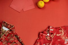 Chinese new year fresh oranges and angpao pocket and qipao on red paper background. Chinese new year fresh oranges and angpao pocket and qipao blossom on red