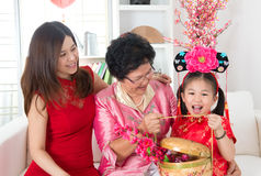 Chinese new year gift. Beautiful grandchild visiting grandparent with gift during Chinese new year festival