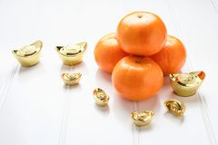 Chinese New year,gold ingots and tangerine oranges on white wood. Table top,Chinese Language ingot mean wealthy Stock Photography