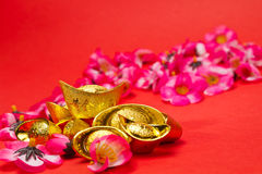 Chinese New Year - Golden Ingots. Golden Ingots whit plum blosoms on red surface and background for Chinese New Year usage vector illustration