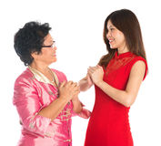 Chinese New Year greeting. Happy Chinese New Year! Chinese senior parent and daughter in traditional Chinese cheongsam greeting to each other, isolated on white