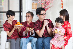 Chinese New Year at home. Celebrating Chinese new year. Happy Asian multi generations family in red cheongsam reunion and greeting at home Stock Photo