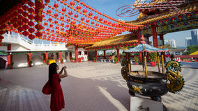 Chinese New Year in Kuala Lumpur. KUALA LUMPUR, MALAYSIA - 18TH FEBRUARY 2015: A woman pray for prosperity with lanterns hanging at Thean Hou Temple during Stock Photography