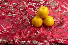 Chinese new year oranges on red Chinese textile background. Chinese new year oranges on red dragon Chinese textile background royalty free stock photography