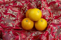 Chinese new year oranges on red Chinese textile background. Chinese new year oranges on red dragon Chinese textile background royalty free stock photos