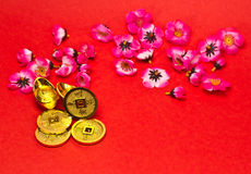Chinese New Year Ornaments III. Golden nuggets and emperors coins with cherry plum blossoms on red surface for Chinese New Year royalty free illustration