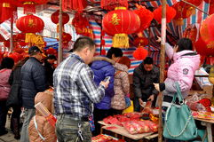 Chinese New Year Outdoor Market. Man checks his cellphone while nearby people shop for Chinese New Year decorations at the outdoor Long Xing Square marketplace Royalty Free Stock Photography
