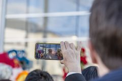 Chinese New Year Parade - The Year of the Dog, 2018. Noisy-le-Grand, France - February 18,2018: Image of a hand of a senior woman filming using a smartphone stock photos
