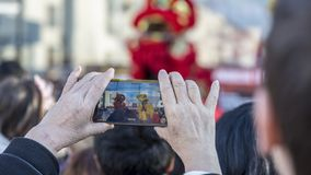Chinese New Year Parade - The Year of the Dog, 2018. Noisy-le-Grand, France - February 18,2018: Image of the hands of a senior woman filming using a smartphone royalty free stock photos