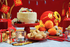 Chinese New Year party table. In red and gold theme with food and traditional decorations Stock Photography
