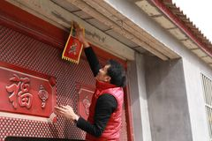 Chinese man post new year`s scrolls , Spring festival couplets and Mars at red door in China Royalty Free Stock Photos