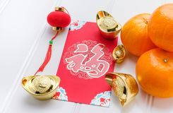 Chinese New year red envelope packet ang pow with gold ingot. S and tangerine on white wood table top,Chinese Language on envelop mean Happiness and on ingot stock photography