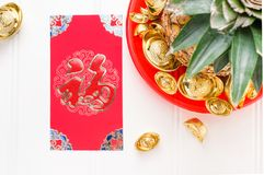 Chinese New year red envelope packet  ang pow  and pineapple w. Ith group of gold ingots in red tray on white wood table.on ingots mean wealthy and on envelop Stock Image