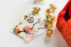 Chinese New year,red envelope packet ang pow and red felt fabr. Ic bag with gold ingots and oranges and flower on white wood table top,Chinese Language mean royalty free stock photo