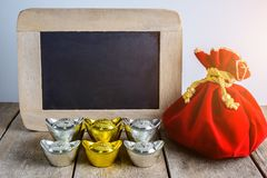 Chinese New Year Red fabric bag, ang pow and chalkboard with Chi. Nese money of luck and Shoe-shaped gold ingot Yuan Bao with Chinese character `Fu` means stock photos