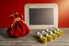 Chinese New Year Red fabric bag, ang pow and chalkboard with Chi. Nese money of luck and Shoe-shaped gold ingot Yuan Bao with Chinese character `Fu` means stock photography