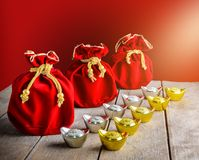 Chinese New Year Red fabric bag, ang pow with Chinese money of l. Uck and Shoe-shaped gold ingot Yuan Bao with Chinese character `Fu` means fortune, Traditional stock photos