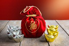 Chinese New Year Red fabric bag, ang pow with Chinese money of l. Uck and Shoe-shaped gold ingot Yuan Bao with Chinese character `Fu` means fortune, Traditional royalty free stock photography