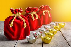Chinese New Year Red fabric bag, ang pow with Chinese money of l. Uck and Shoe-shaped gold ingot Yuan Bao with Chinese character `Fu` means fortune, Traditional stock photography