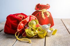 Chinese New Year Red fabric bag, ang pow with Chinese money of l. Uck and Shoe-shaped gold ingot Yuan Bao with Chinese character `Fu` means fortune, Traditional stock images