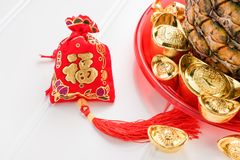 Chinese New year red felt bag ang pow and pineapple with gro. Up of gold ingots in red tray on white wood table.on ingots mean wealthy and on bag mean happiness royalty free stock photos