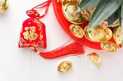 Chinese New year red felt bag ang pow and pineapple with gro. Up of gold ingots in red tray on white wood table.on ingots mean wealthy and on bag mean happiness royalty free stock images