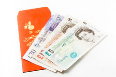 Chinese New Year Red Packet or Angpow with Pound. Sterling banknotes royalty free stock images