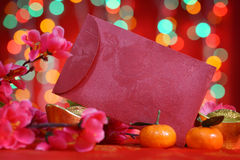 Chinese new year red packet. Chinese new year festival decorations, ang pow or red packet with copy space ready for text, on glitter red background Stock Photos