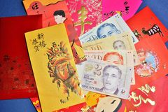 Chinese Red packets and money. Variety of Chinese New Year Ang Pows and some Singapore bank notes Stock Image