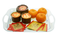 Chinese New Year rice cakes and oranges. Chinese New Year rice cakes, oranges and red packets on a serving tray Royalty Free Stock Photos